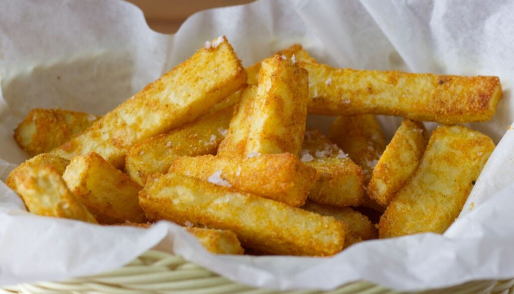 A basket of fries fresh from the oven sprinkled with salt.