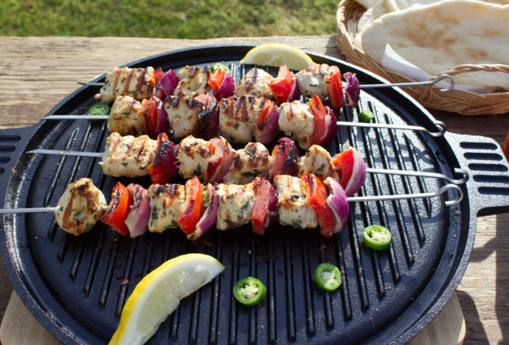 Skewers with meat and veg cooking on a griddle outdoors.