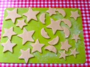 Cookie dough stars on a silicone mat.
