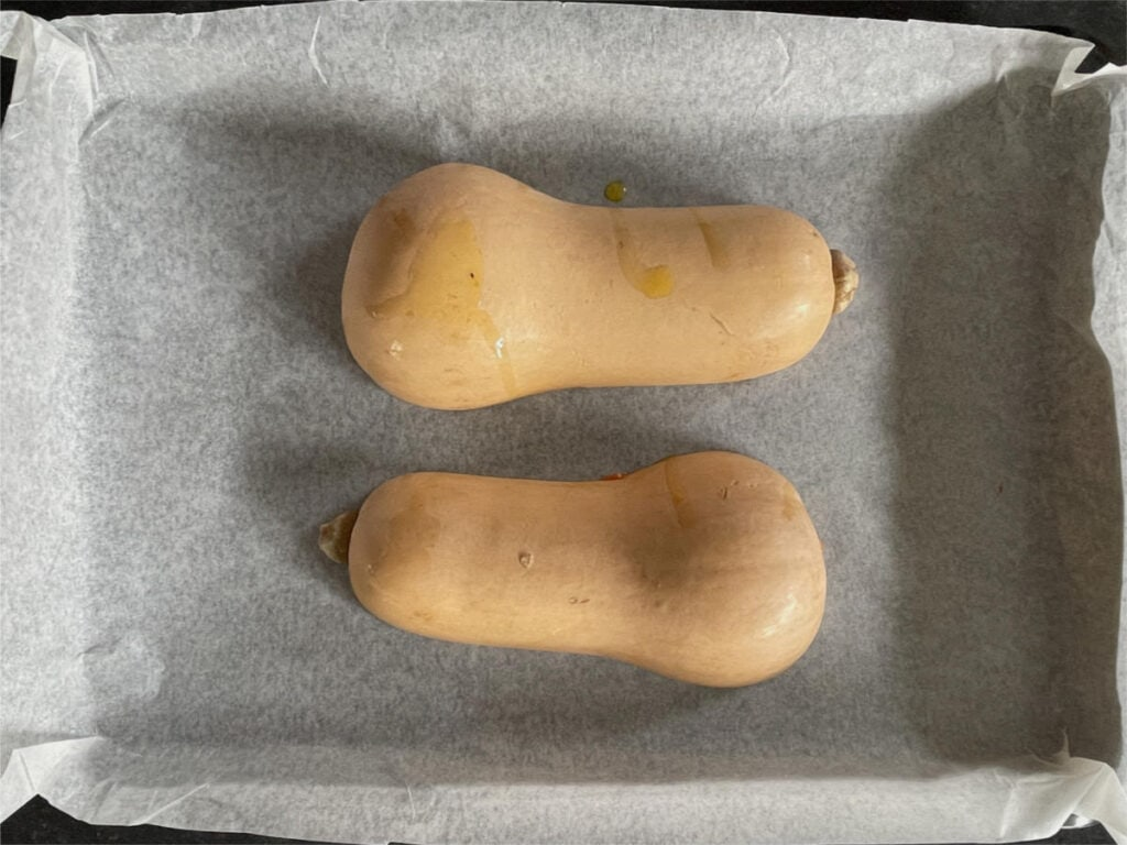 Two halves of butternut squash face down on a baking tray.