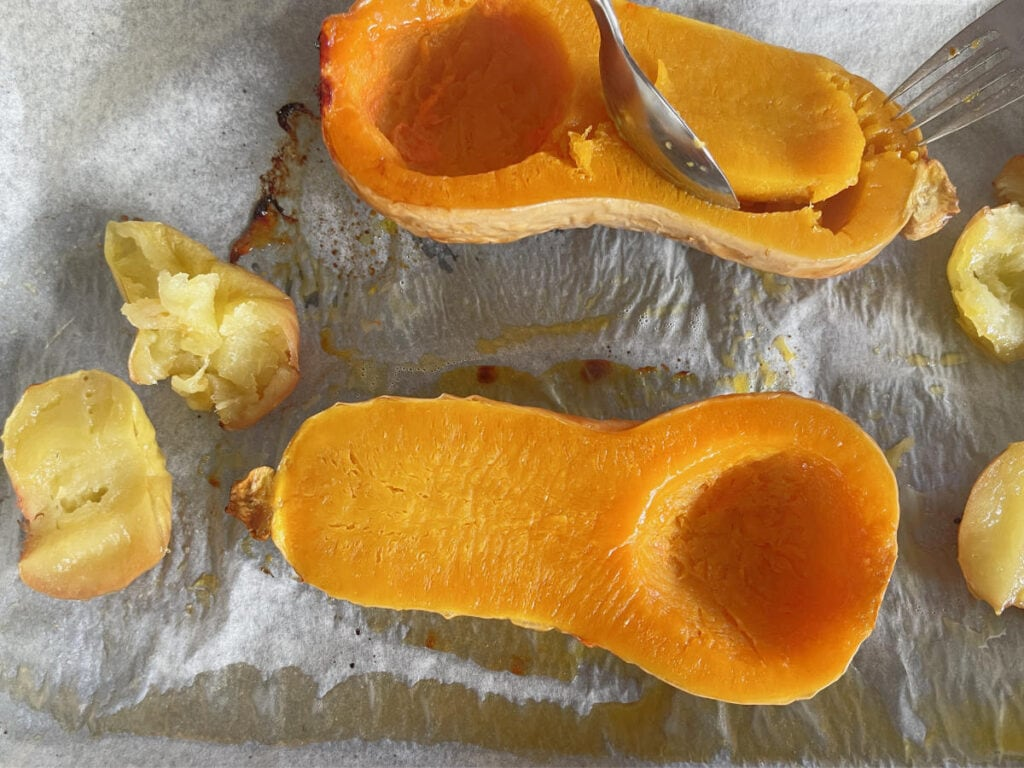 A spoon scooping out the flesh of roasted butternut.