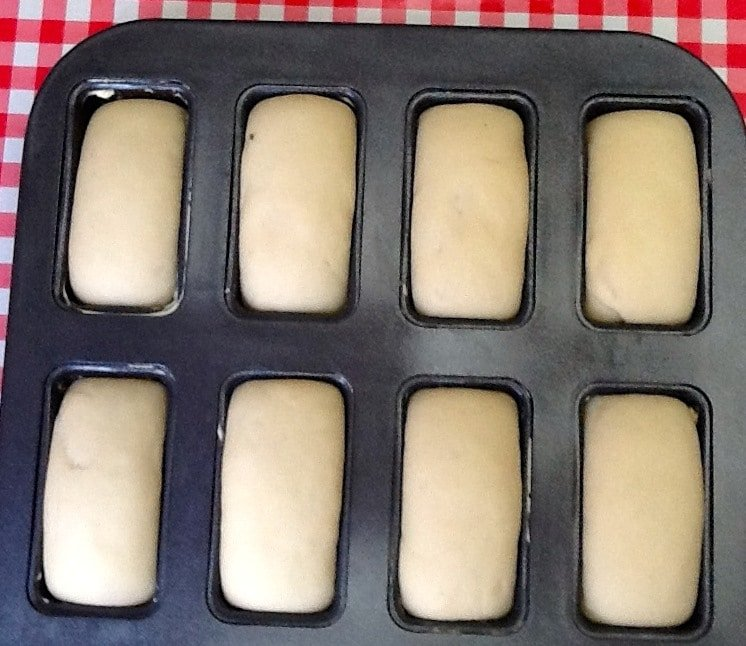 Mini loaf tin filled with risen dough.