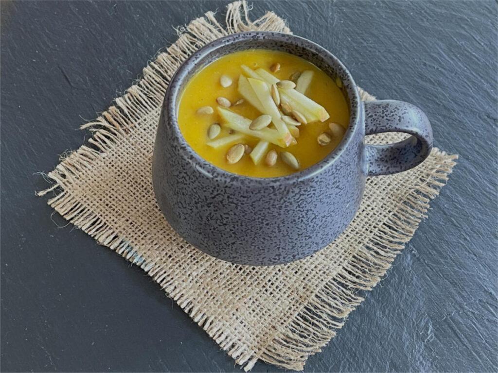 A mug of Roasted Squash and Apple Soup on a hessian mat.