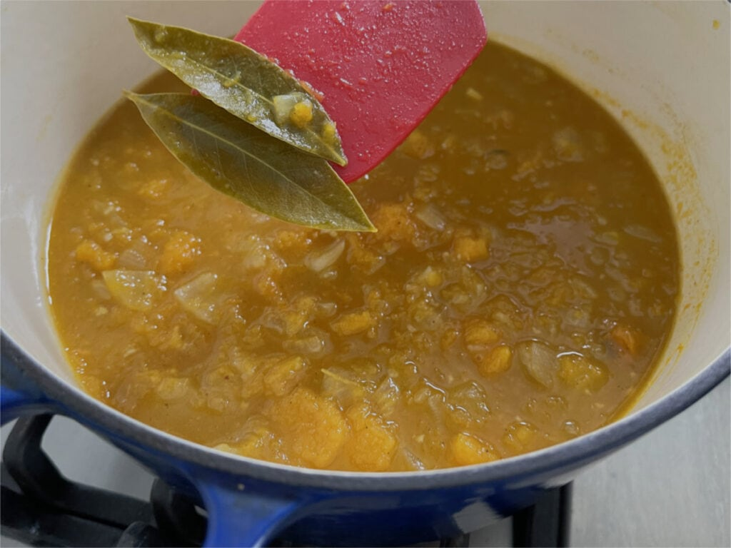 A spatula taking out the bay leaves from the soup in the pan.