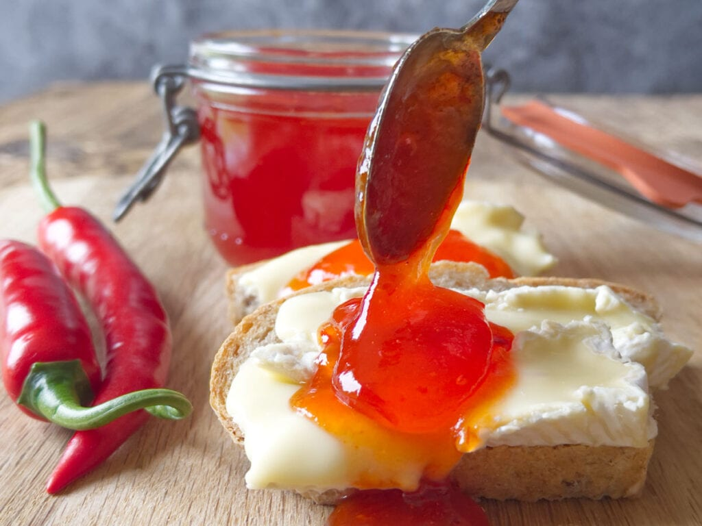 A spoon of chilli jam placed on cheese and bread with a jar behind it.