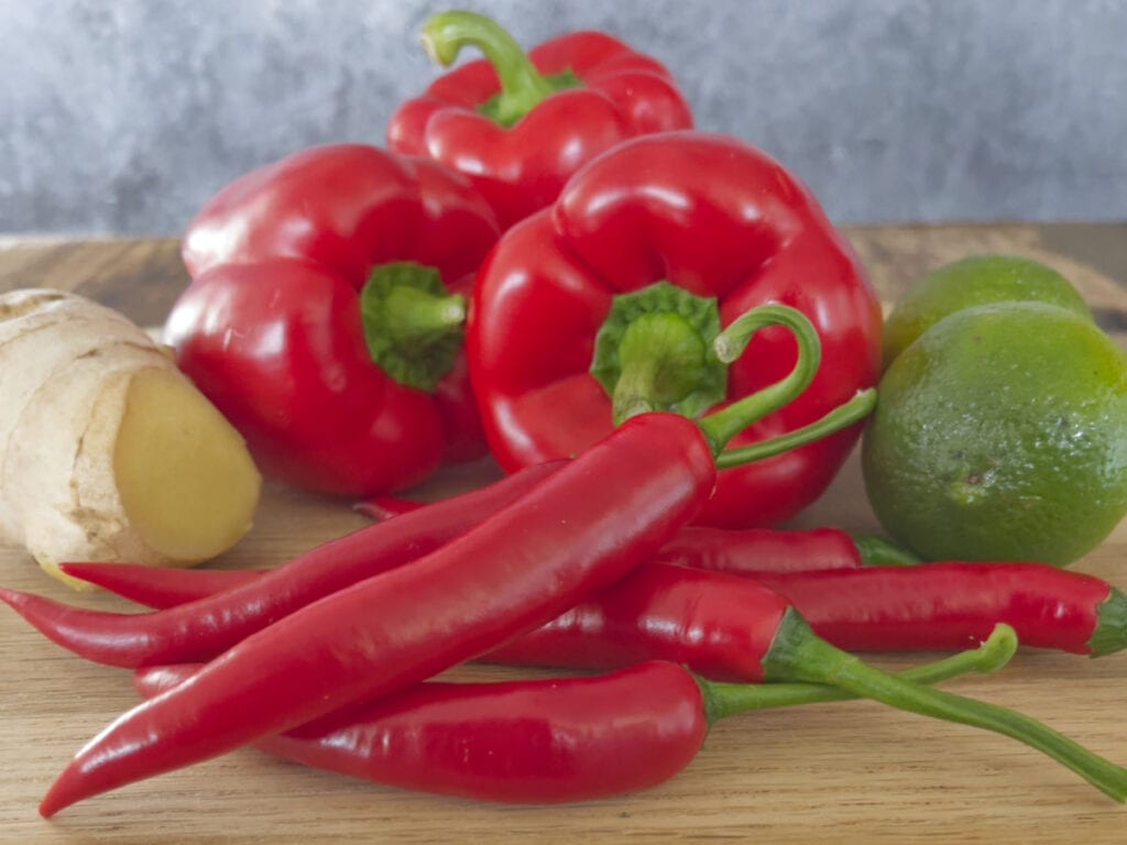 Fresh ingredients for chilli jam. Ginger, red peppers, limes and chillies on a table.