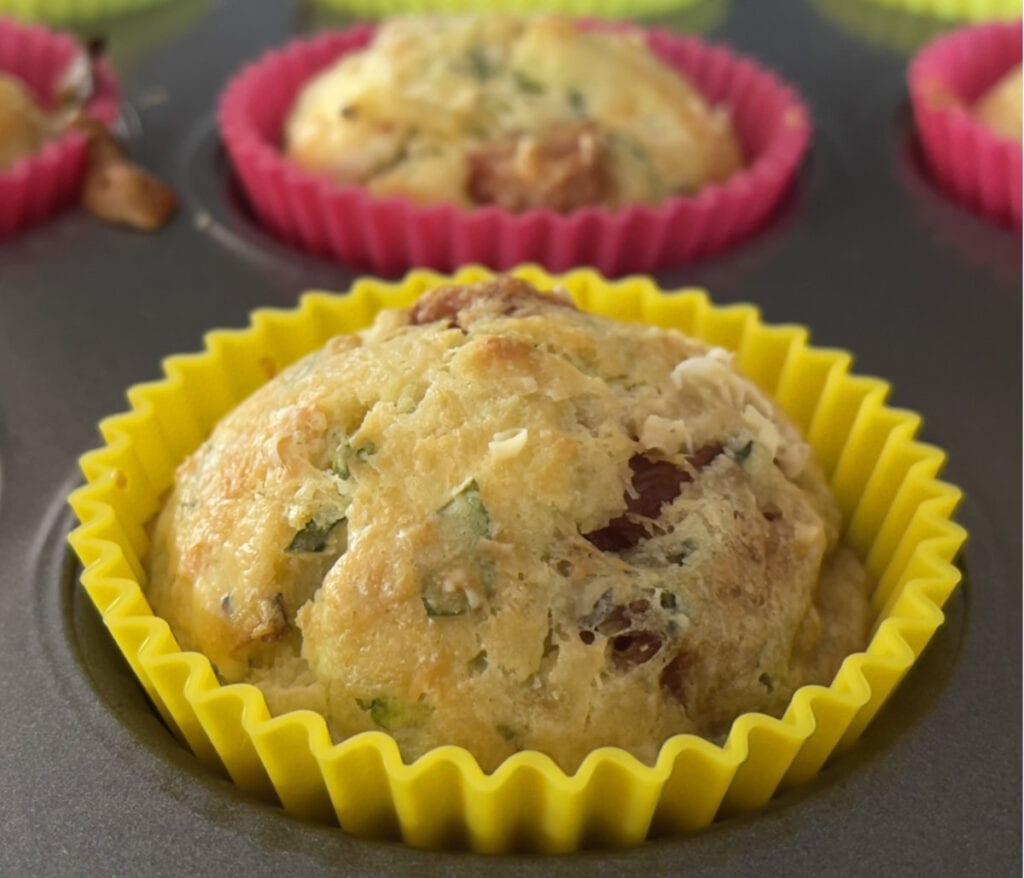 Courgette, Roasted Red Pepper & Feta Muffins in a muffin tin.