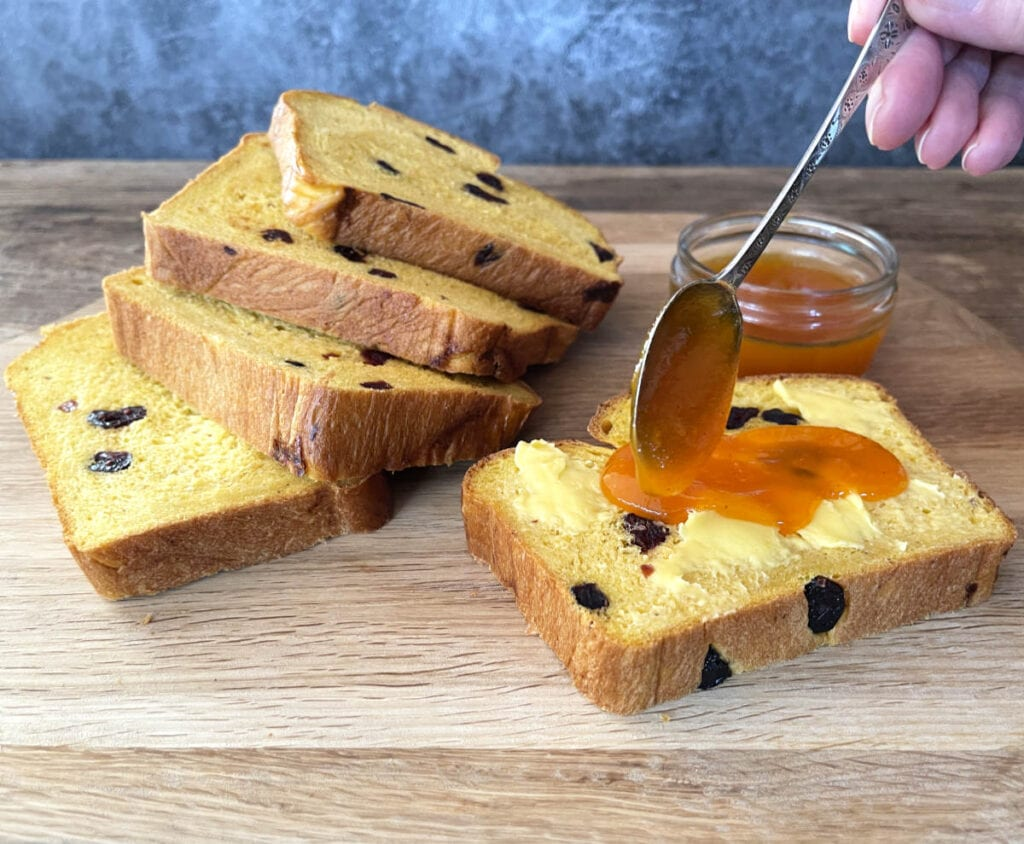 Slices of pumpkin bread with a pot of pumpkin jam.