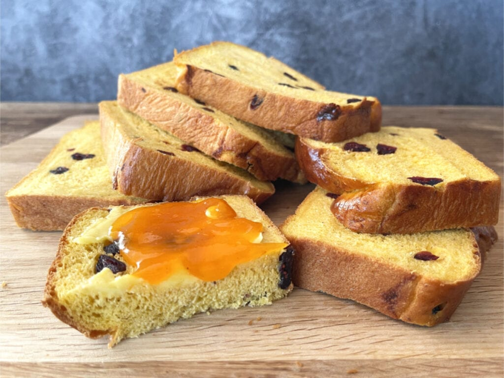 Slices of pumpkin loaf on a wooden board with one slice buttered and jam on it.