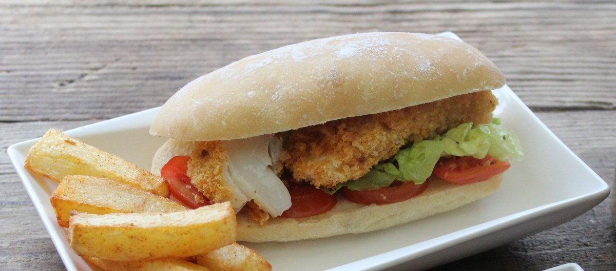 Jumbo Cod Fish Fingers in a homemade roll with a side of oven baked chips
