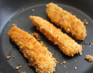 Jumbo Cod Fish Fingers frying in a pan.