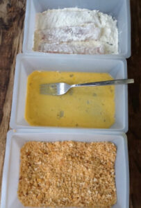 Assembly line of shallow dishes with flour mix, beaten egg and golden breadcrumbs ready to make fish fingers