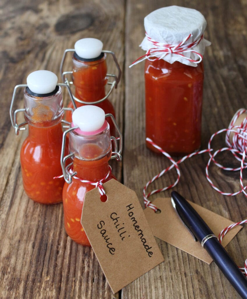 Bottles of chilli sauce with a label, string and a pen.