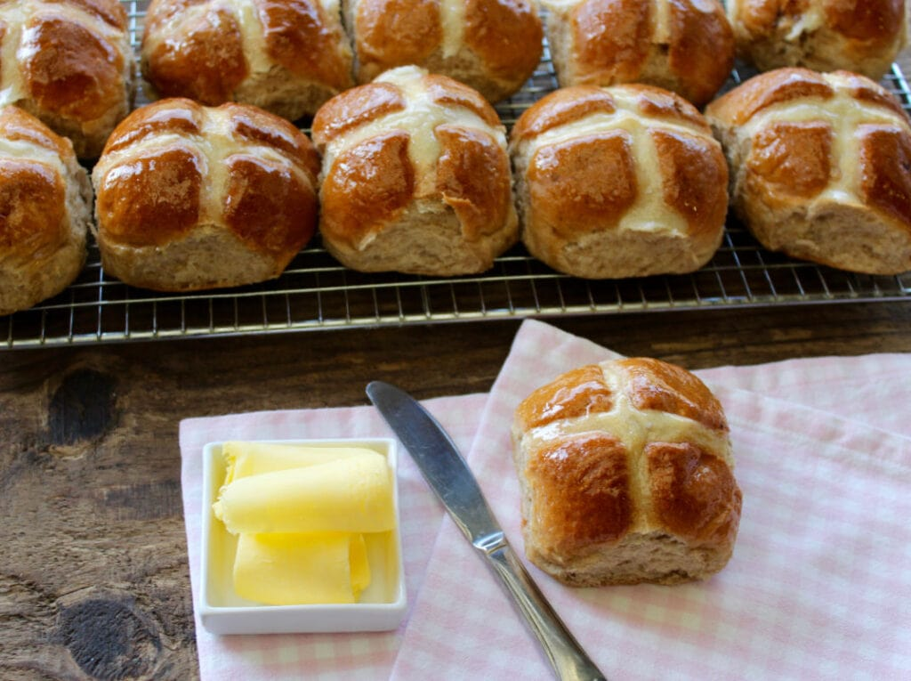 Buns ready to be buttered with butter and knife and napkin.
