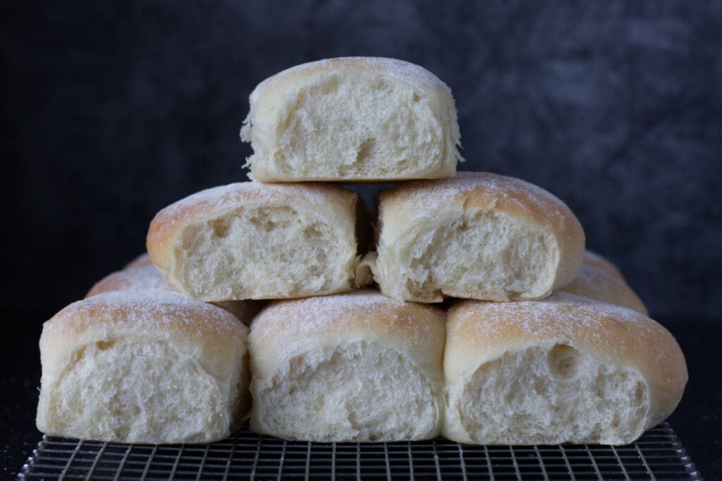 Soft Bread Rolls in a stack on a cooling rack.