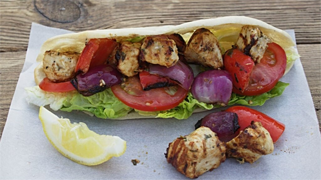 Salad, a slice of lemon with chicken, onions and peppers in a pitta bread.
