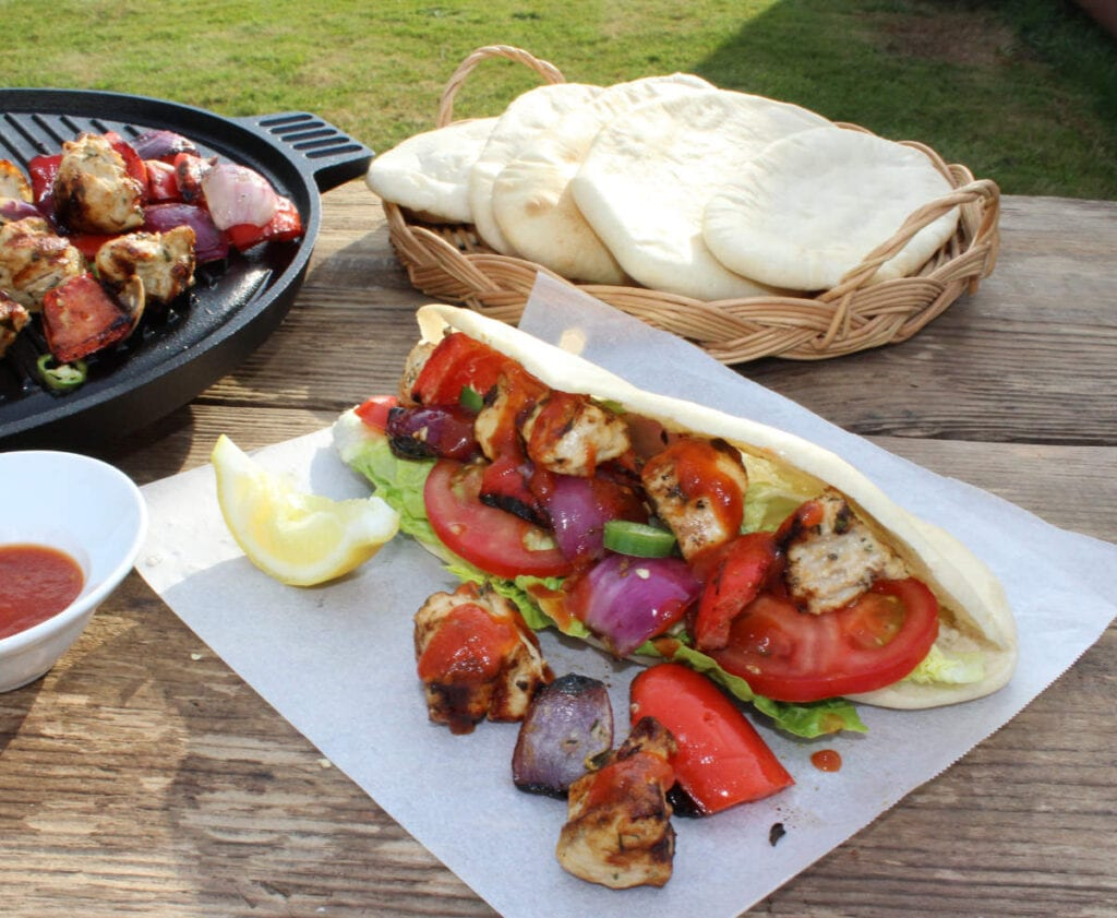 A filled pitta served on baking parchment with a basket of pittas, a bowl of chilli sauce alongside a griddle with meat and vegetables cooking.