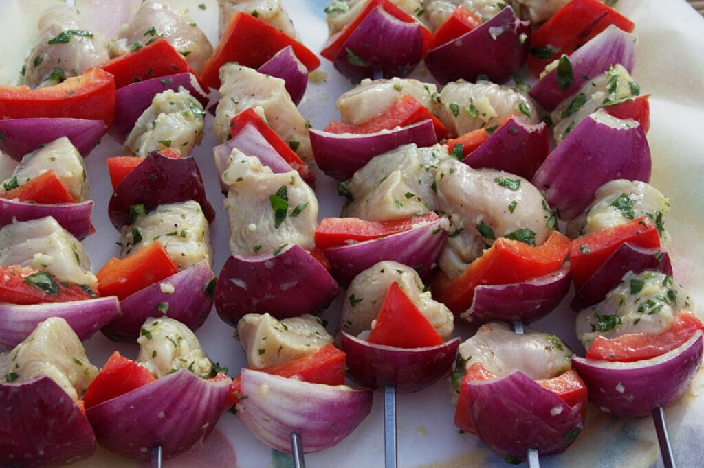 Marinated cubes of meat with chunks of pepper and onion on skewers.