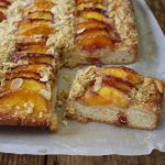 Peach Streusel Traybake is a yeast cake with a cinnamon crumble & juicy peach topping. Delicious on its own or served warm with a dollop of cream or custard.