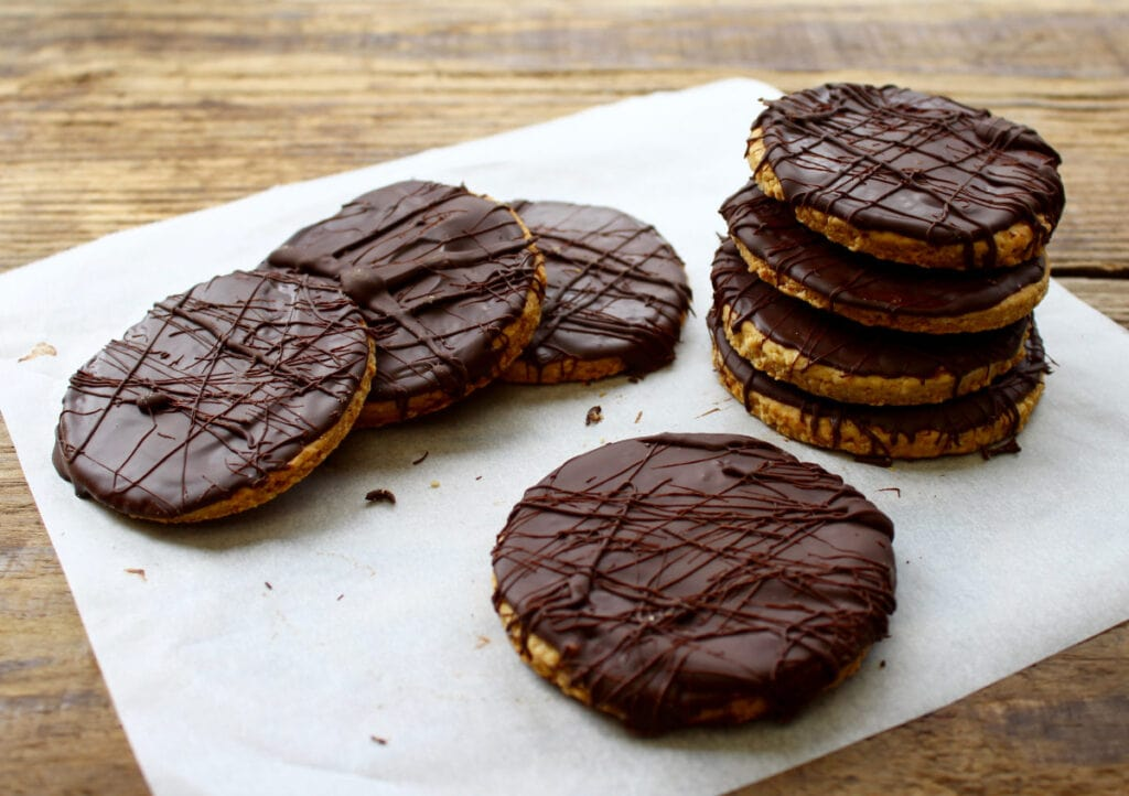 A pile of dark chocolate digestives on baking parchment.