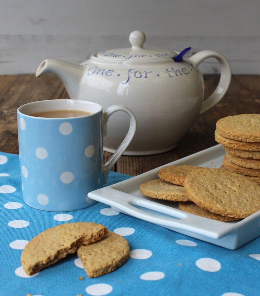 A teapot, a mug of tea and a tray of homemade cookies.