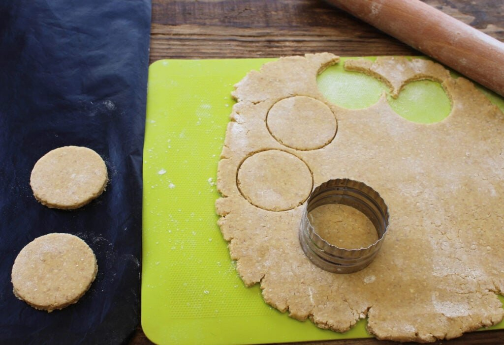 A silicone mat with cookie dough and a cookie cutter and rolling pin.