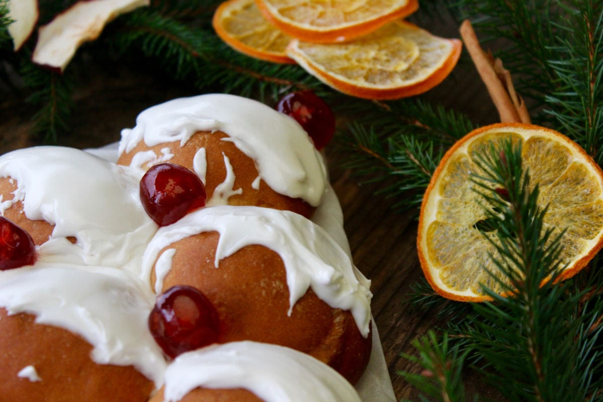 Fruited buns with icing and decorated with cherries next to dried orange slices and cinnamon