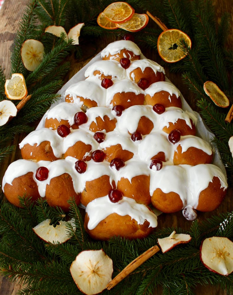 Christmas Tree Bread on a festive table decorated with branches, orange slices, apple slices and cinnamon sticks