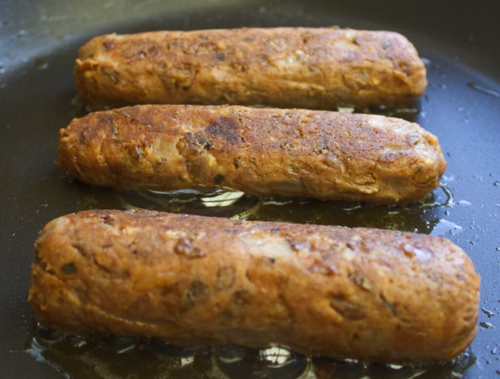 Vegetarian sausages frying in a pan.