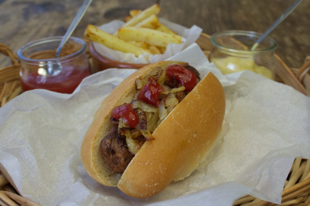 Homemade Vegetarian Sausage served in a Hot Dog Roll with chips.