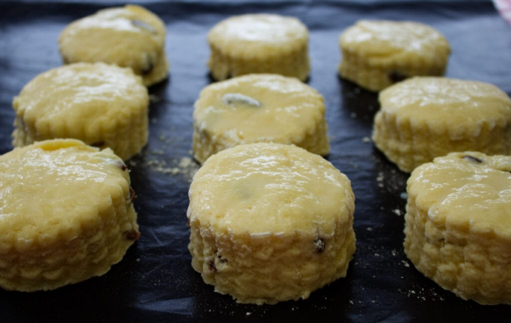Scones brushed with egg wash on a baking tray.
