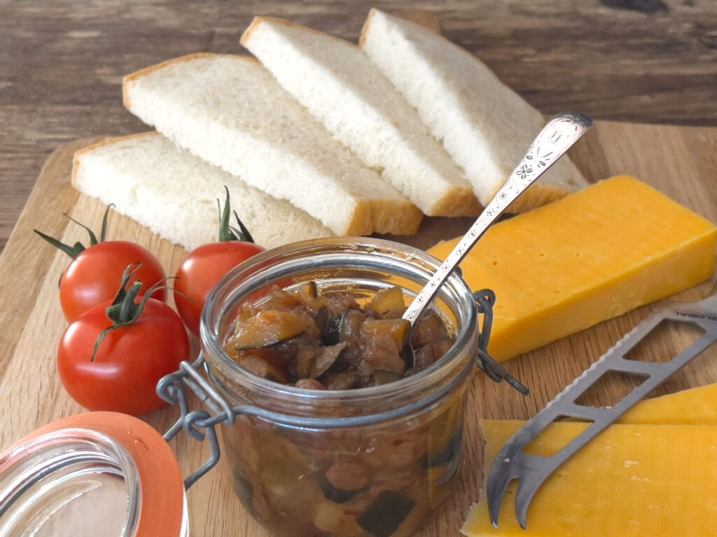 An opened  jar of spicy courgette chutney on a wooden board with bread, cheese and tomatoes.