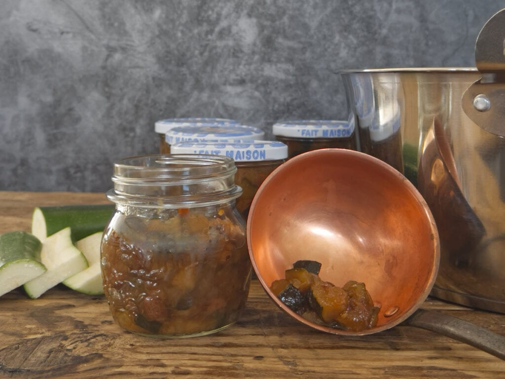 Jars of chutney with an opened jar and a ladle.