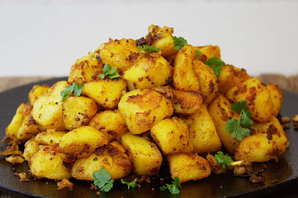 A pile of roasted Indian potatoes on a griddle.