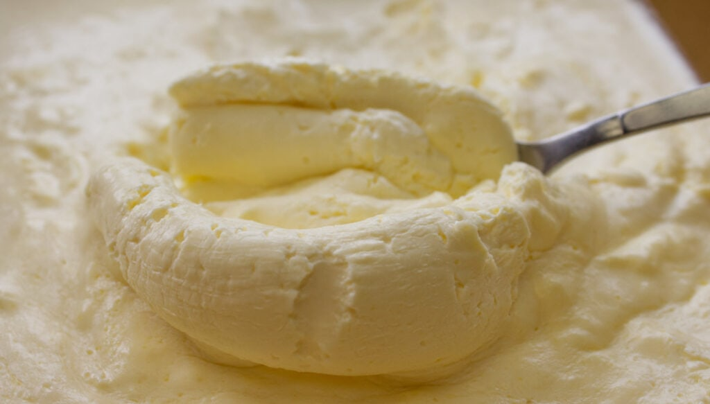 A close up image of a scoop of thick buttery cream.