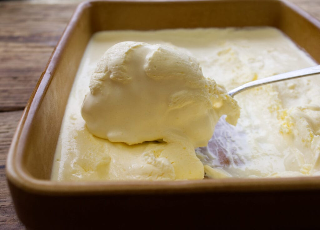Large shallow ceramic dish filled with clotted cream and a spoonful being taken out.