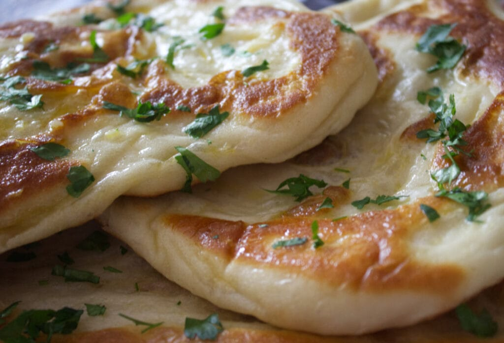 Close up image of buttered flatbread with freshly chopped coriander.