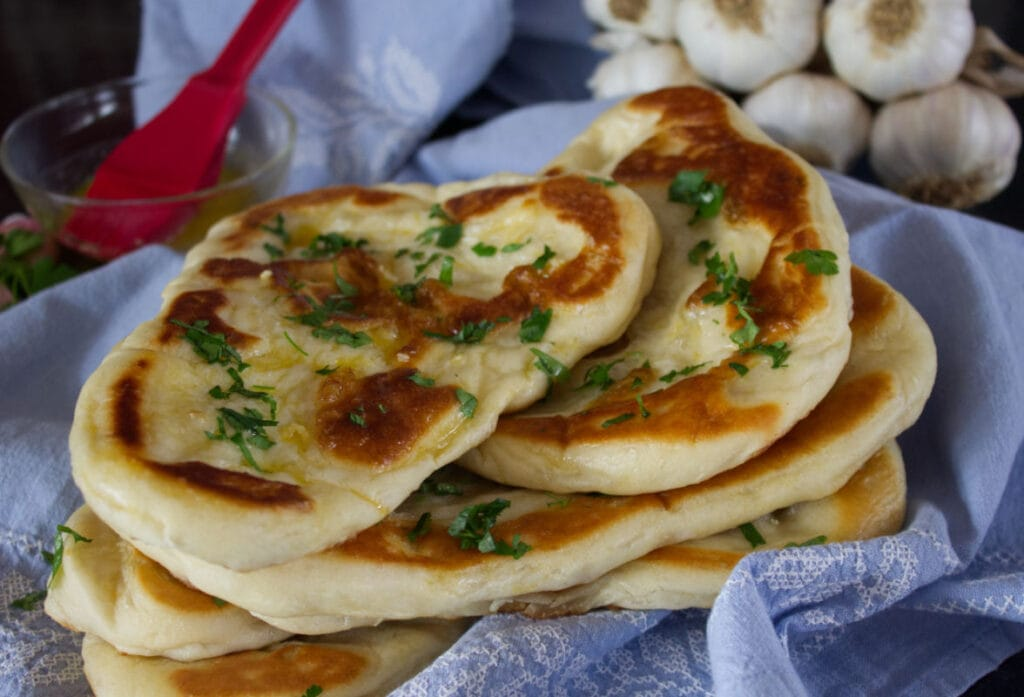Buttered Indian Flatbread in a blue cloth.