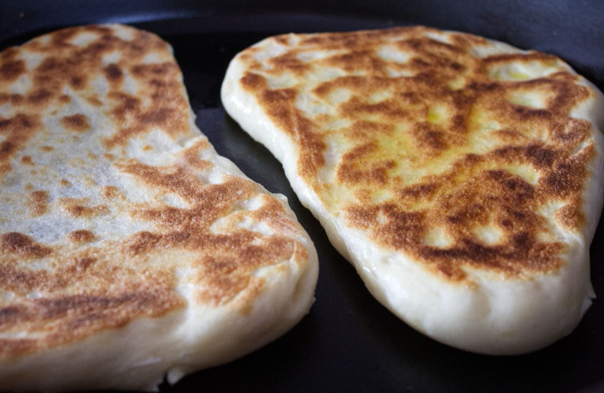 Two flatbreads nicely browned and turned over to cook the other side.