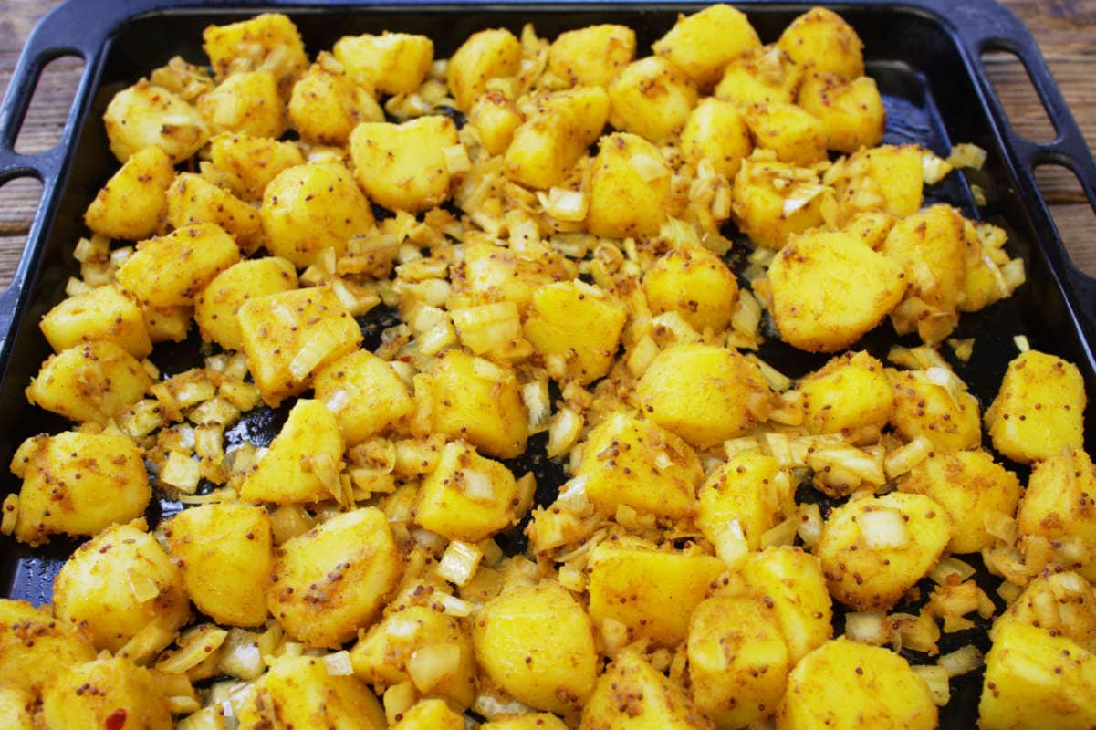 Spiced potatoes on a roasting tray for Easy Bombay Potatoes .