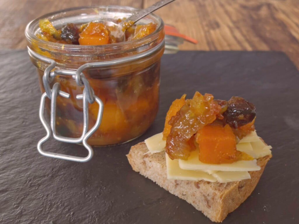 A jar of opened chutney and a spoon with a piece of bread and cheese.