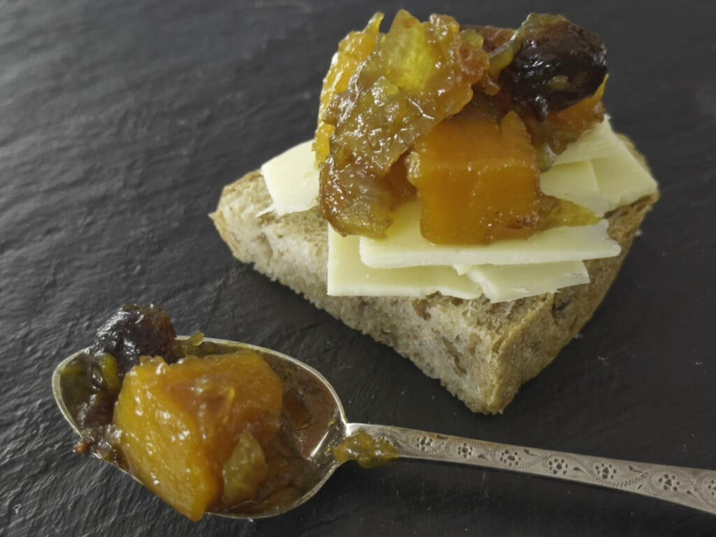 A spoon of chutney next to a slice of bread and cheese with chutney on it.