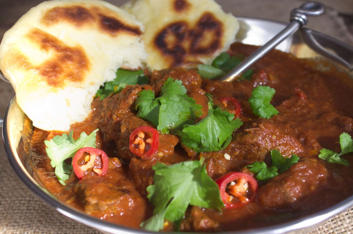 Beef Madras served in a Balti dish with Homemade Naan Bread.
