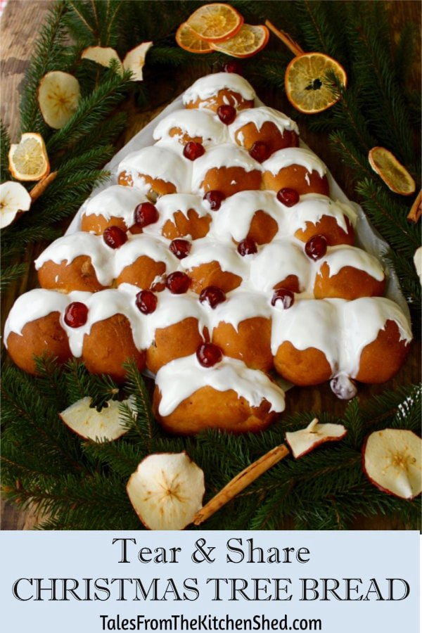 Spiced fruit buns decorated with snowy icing and glace cherries.