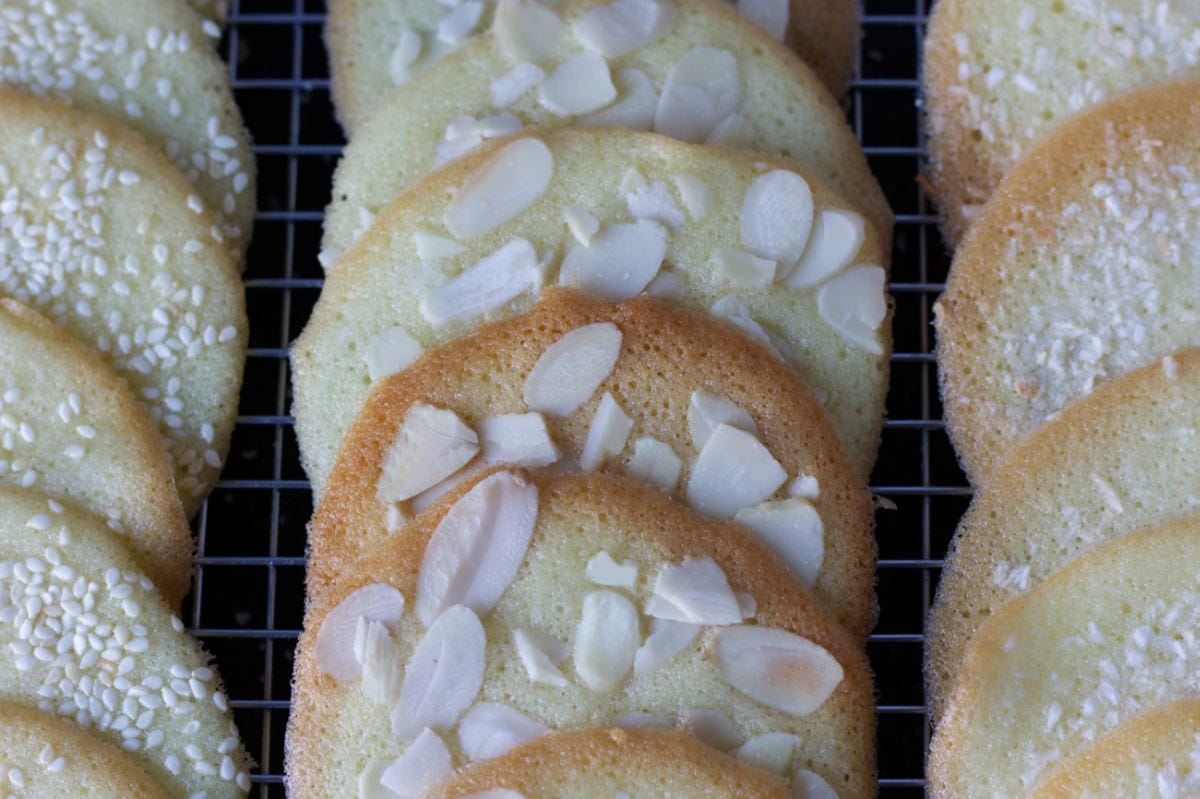 Close up image of almond, sesame and coconut tuiles on a cooling rack.
