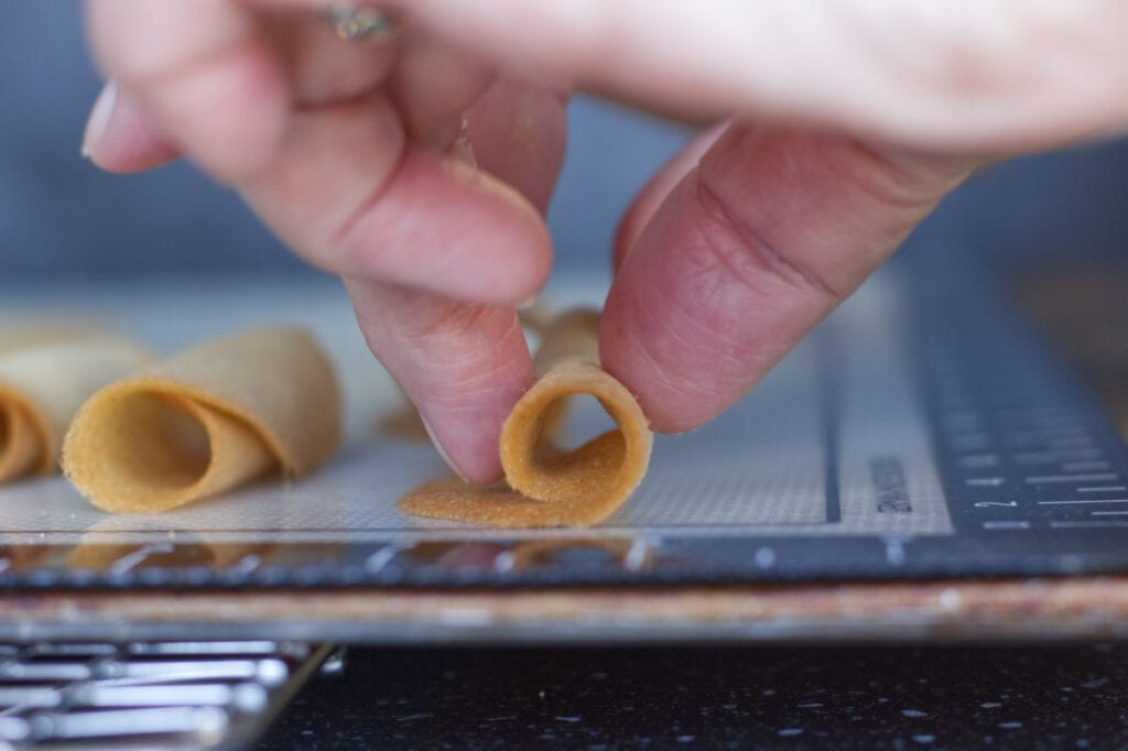 Close up image of a tuile being rolled whilst it is hot by the author of the Tuiles Recipe.