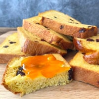 Slices of pumpkin bread with a slice buttered.