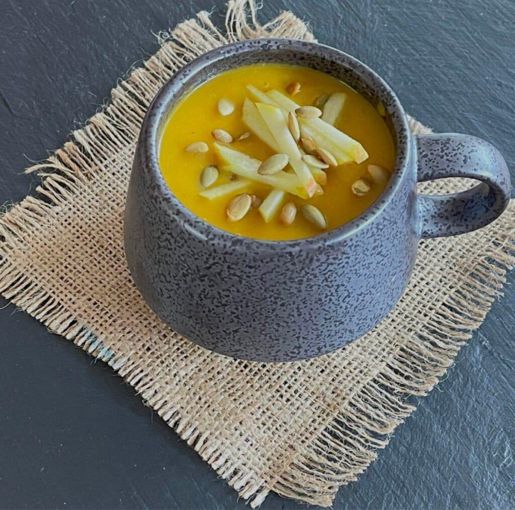 A mug of soup on a hessian mat.