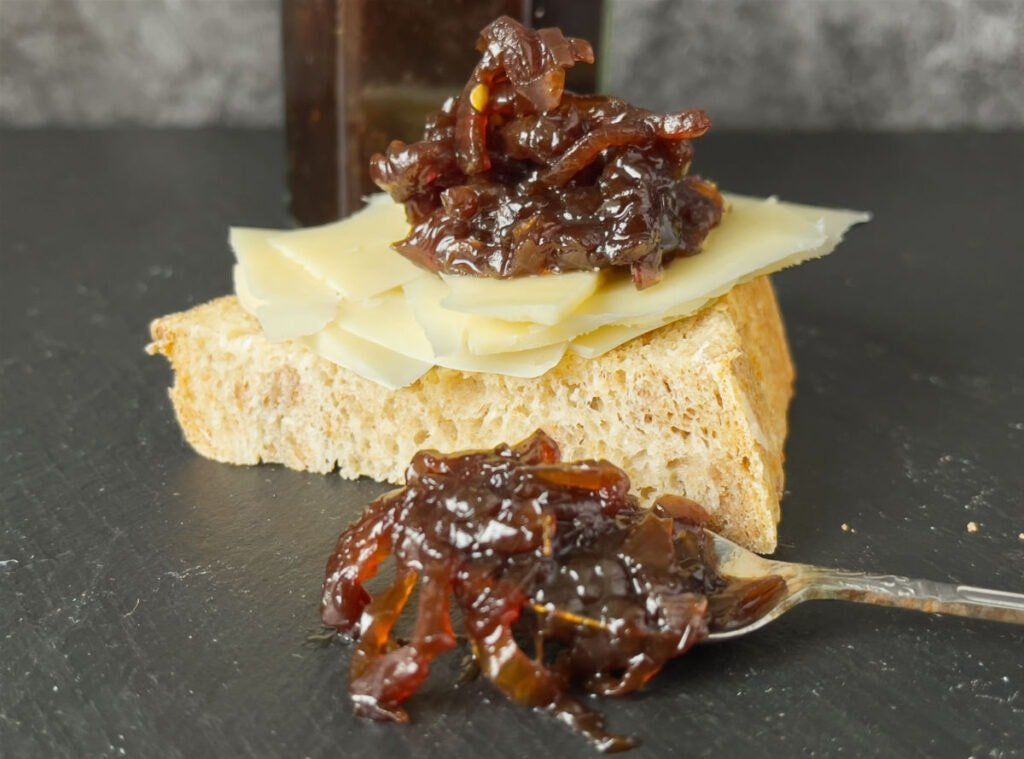 A slice of bread and cheese with a spoon of onion jam.