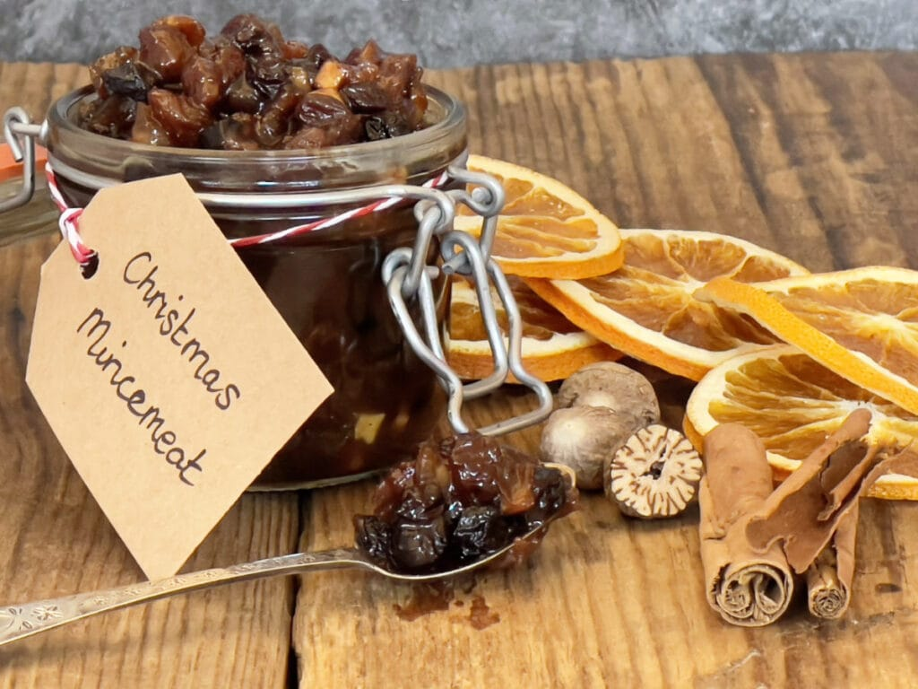 An open jar of mincemeat with a spoon surrounded by dried orange slices and spices.